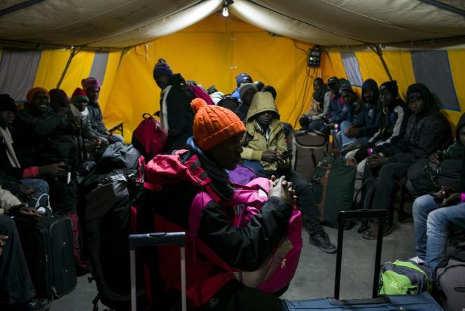 Les migrants attendent dans un hangar le bus qui les mènera dans un centre d'accueil et d'orientation.