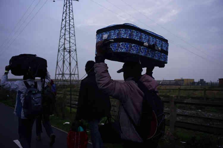 Les migrants arrivent par petits groupes vers le point de départ des bus.