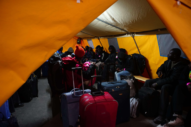 Le 24 octobre, les migrants qui ont décidé de partir de la « jungle » attendent sous une tente le bus qui les mènera vers un centre d'accueil et d'orientation.