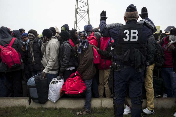 Des centaines de réfugiés attendent de monter dans l'un des bus qui les emmènera vers un centre d'accueil et d'orientation (CAO), le 24 octobre 2016 aux abords de la « jungle» à Calais.