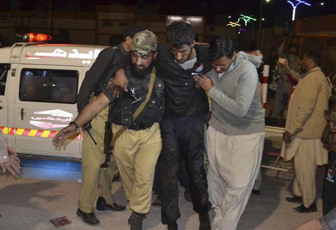 Un volontaire et un policier évacuent un blessé vers l'hôpital, à Quetta, le 24 octobre.