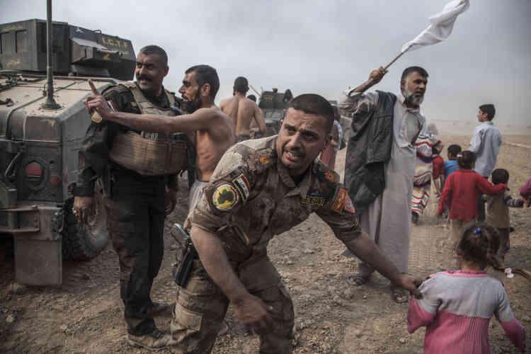 Le major Salam avec ses troupes de la Division d'or mettent à l'abrihommes, femmes et enfants, pendant le feu incessant des mitrailleuses des Humvee qui contre les tirs de sniper de l'EI. A Tarbazawah,le 24 octobre.