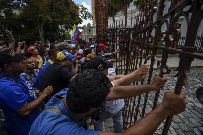 Des partisans du président Maduro tentent de pénétrer dans l'enceinte de l'Assemblée nationale, le 23 octobre, à Caracas.