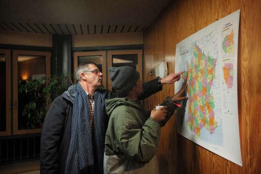 """Pierre-Yves Mahieu, le maire de Cancale, montre à un réfugié soudanais la position géographique de sa commune. Quarante-sept Soudanais, deux Erythréens et un Afghan ont quitté la """"jungle"""" de Calais dans l'après-midi pour rejoindre ce CAO de Bretagne."""