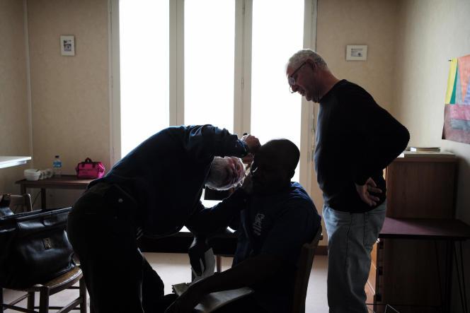Deux médecins bénévoles auscultent un réfugié soudanais souffrant de perte d'audition.