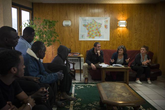 La chef de service de l'association Coallia, Armelle Musellec (au centre), explique aux réfugiés soudanais, érythréens et afghans arrivés la veille les règles de vie du centre d'accueil et d'orientation (CAO) de Cancale dans lequel ils vont résider.