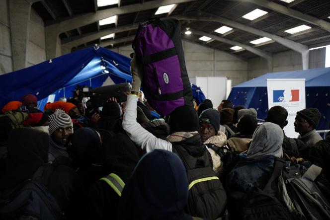 Des migrants se pressent pour se faire enregistrer et monter dans un bus, le 24 octobre.