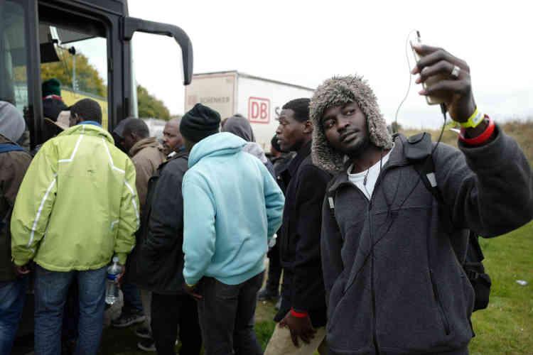 Un réfugié soudanais se prend en photo tandis que d'autres remontent dans leur bus, après leur pause déjeuner sur une aire d'autoroute, sous la surveillance de la gendarmerie.