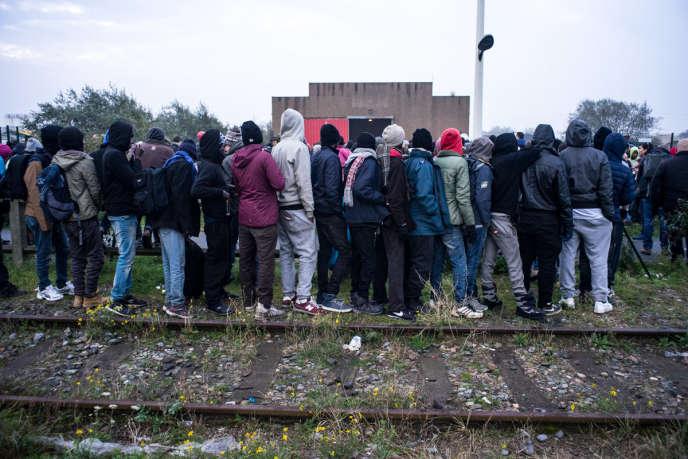 La file d'attente des mineurs isolés déborde jusque sur les vieux rails SNCF, lundi 24 octobre, au premier jour de l'opération de démantèlement de la « jungle» de Calais.