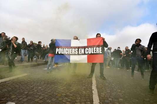 Des policiers posent près d'un fumigène lors d'un rassemblement organisé hors du cadre syndical devant l'Assemblée nationale, le 25octobre.