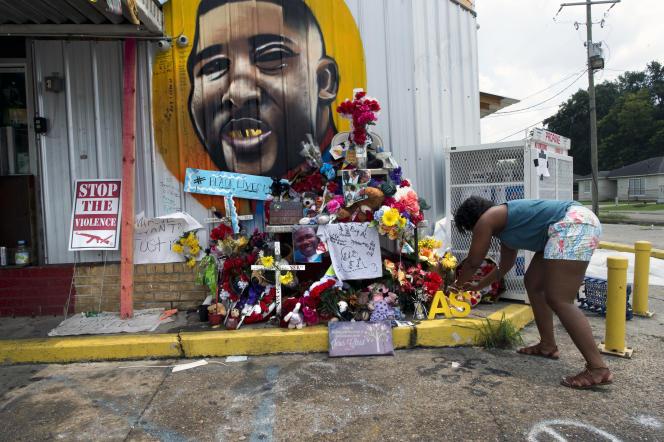 Une femme dépose les initiales peintes en jaune A. S., devant un sanctuaire improvisé en mémoire d'Alton Sterling, à proximité du magasin Triple S Convenience de Bâton-Rouge où il a été abattu par la police, le 5 juillet 2016.