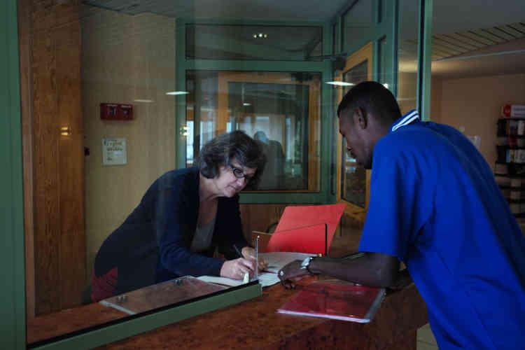 Un réfugié soudanais montre ses documents administratifs à Armelle Musellec, cheffe de service de l'association Coallia.