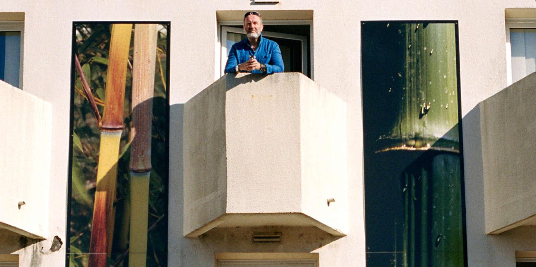 Serge Joncour observe la vue imprenable sur le parking du centre commercial depuis le balcon de sa chambre d'hotel