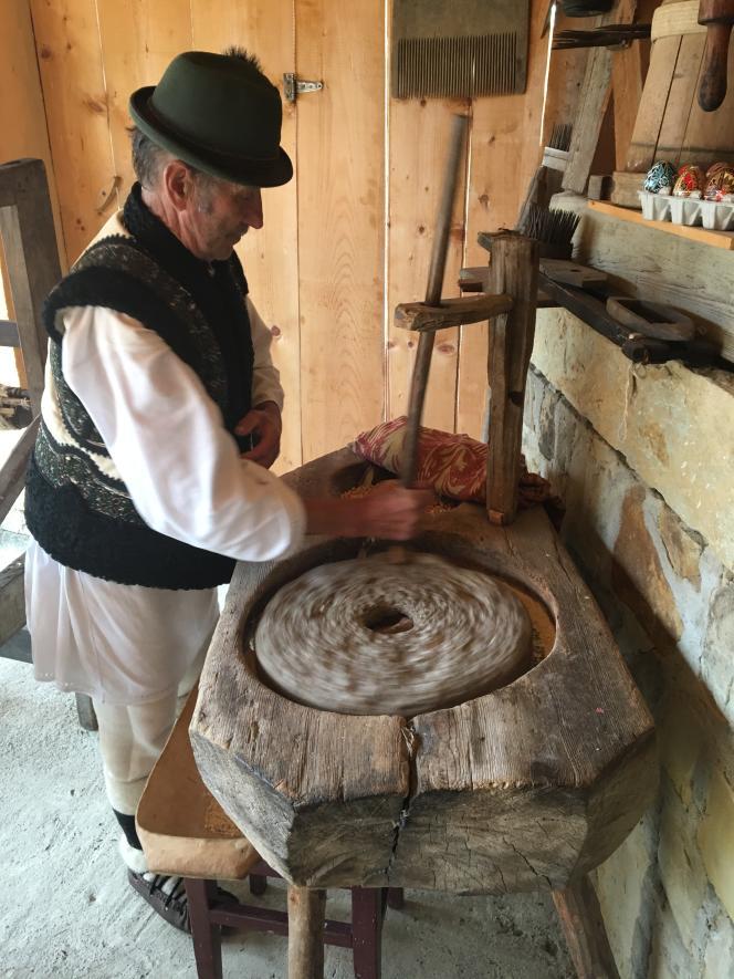 Paysan houtsoule en costume traditionnel devant son moulin à farine.