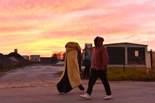 Des migrants marchent au coucher du soleil dans la jungle de Calais, le 27 octobre 2016.