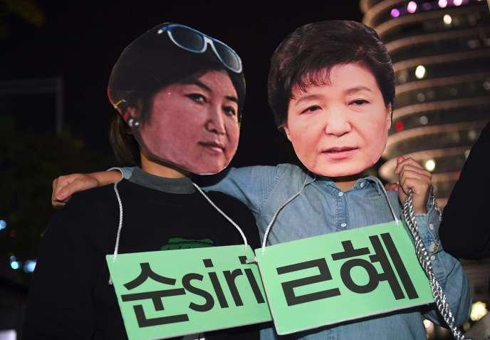 Des manifestants portent des masques figurant Choi Soon-sil et la présidente Park Geun-hye, à Séoul, le 27 octobre.