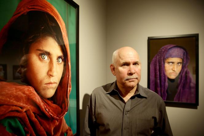 Steve McCurry, qui pose entre la photo de la« jeune Afghane» prise en 1984, à gauche, et celle prise en 2002, à droite.