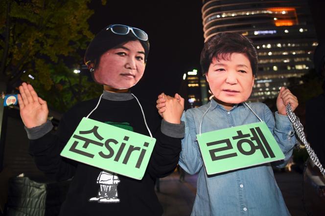 Deux manifestants portent des masques de la président sud-coréenne Park Geun-hye et de sa confidente Choi Soon-sil, le 27 octobre à Seoul.