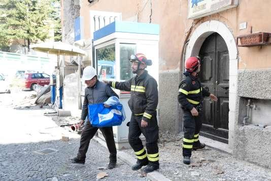 Des pompiers aident les habitants de Visso, dans le centre de l'Italie, à évacuer leur logement, le 27 octobre, au lendemain du séisme.