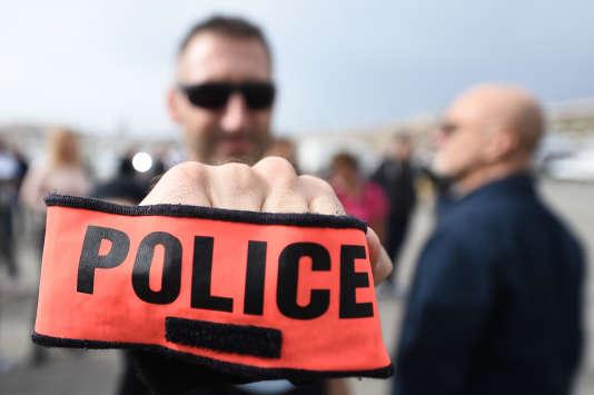 Un policier marseillais brandit son brassard lors d'un rassemblement sur le Vieux-Port, le 26octobre.