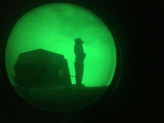 Un soldat des forces irakienne en observation sur un tank, vu d'une lunette de vision nocturne.