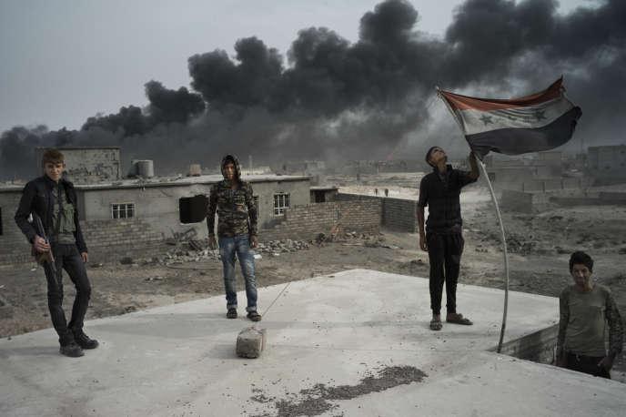 Des miliciens sunnites brandissent un drapeau de l'Irak de Saddam Hussein, le 28 octobre, à Al-Qayyarah.