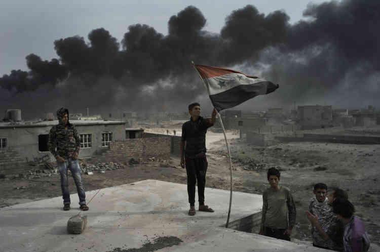 De jeunes hommes armés de kalachnikovs viennent de prendre possession d'une maison, où ils entendent ouvrir un point de contrôle. Sur le toit, ils ont hissé le drapeau irakien de l'époque de Saddam Hussein.
