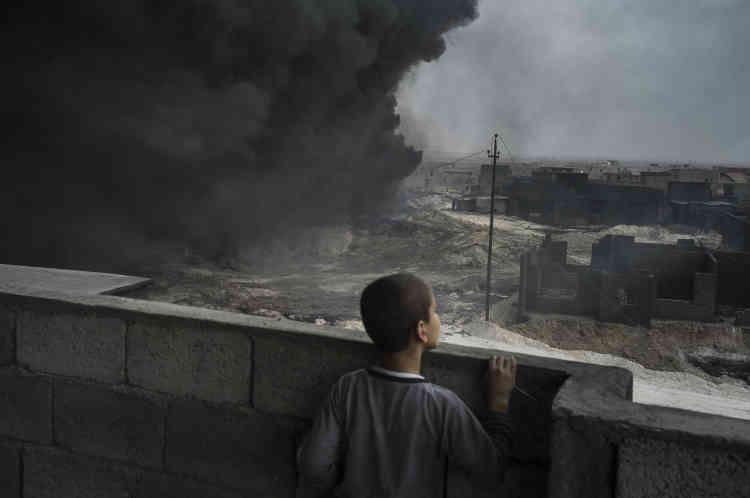Un jeune garçon observe les émanations de fumée du toit d'une maison.