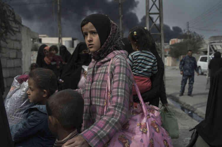 Femmes et enfants de la localité d'Al-Choura suivent l'avancée de l'armée irakienne, pour trouver refuge dans Al-Qayyarah.