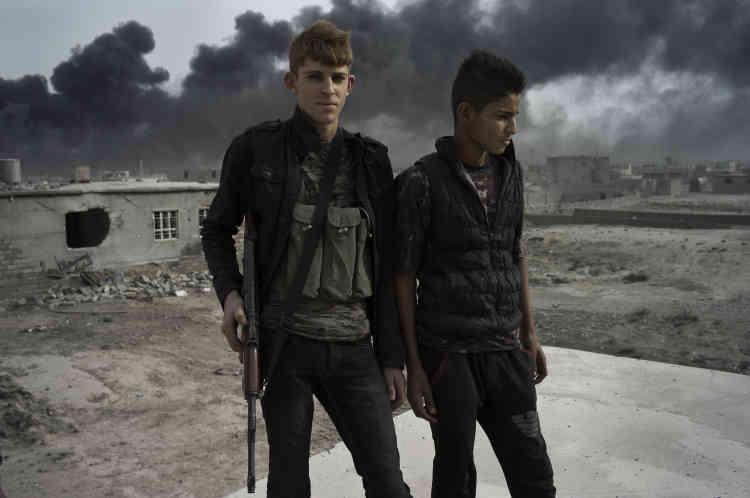De jeunes hommes en civil, armés de kalachnikovs. Certains ont revêtu des vêtements avec des imprimés camouflage.Ils appartiennent à la Mobilisation tribale, un regroupement de milices sunnites locales censées maintenir l'ordre aux côtés des forces de sécurité irakiennes, majoritairement chiites.
