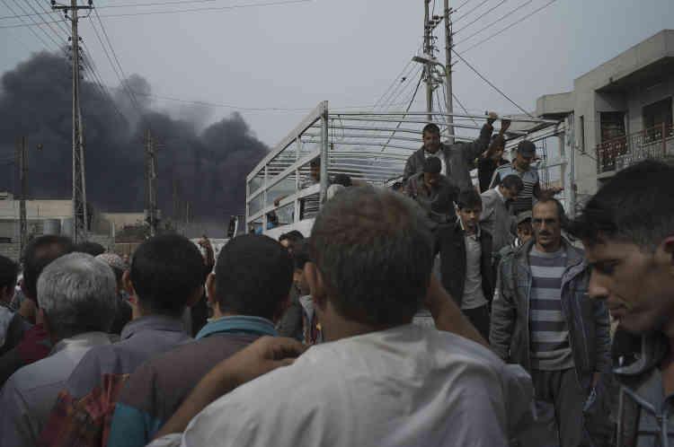 Les civils, qui fuient l'organisation Etat islamique, tentent de monter dans les camions ouverts pour rejoindre une mosquée de quartier, puis, plus tard, aller s'installer dans des camps à la périphérie de la ville.