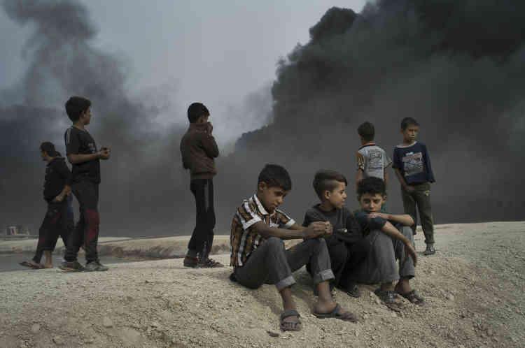 Des enfants aux visages et aux membres recouverts d'une substance sombre et huileuse jouent dans les ruelles aux caniveaux d'eau noire.