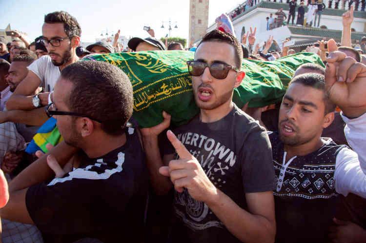 Des manifestants portent le cercueil de Mouhcine Fikrihappé par une benne à ordures alors qu'il tentait de s'opposer à la saisie et à la destruction de sa marchandise par des agents de la ville d'Al-Hoceima, dimanche 30 octobre.