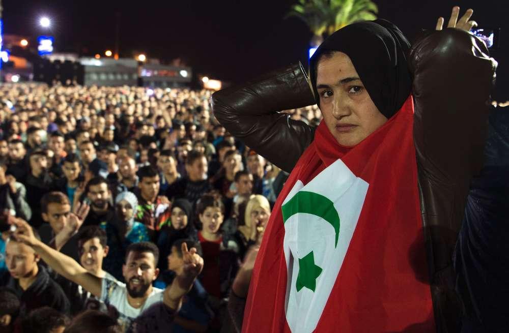 Une jeune manifestante porte le drapeau de la République du Rif, en place de 1921 à 1926.