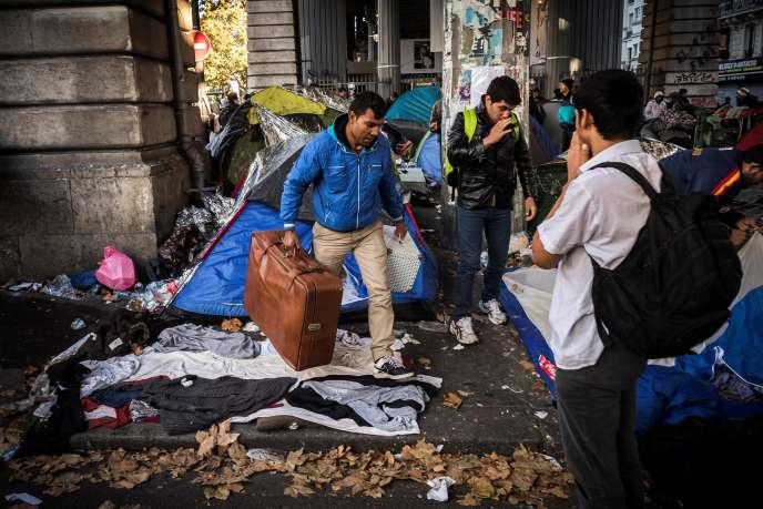 Des migrants récupèrent leurs affaires après l'opération de police, au campement du boulevard de laVillette, à Paris, le 31octobre.