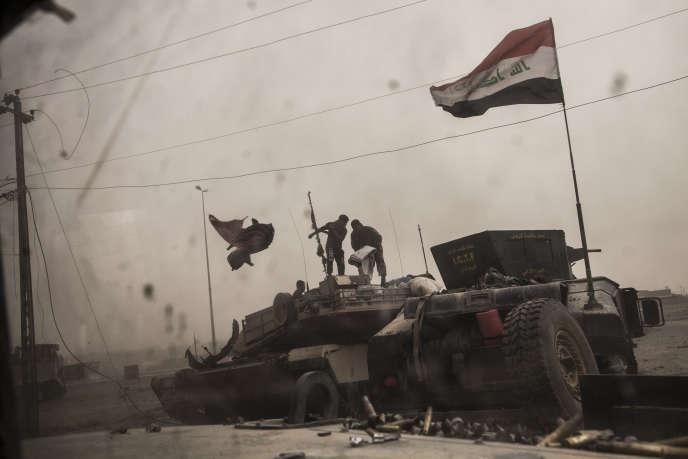 Les conducteurs sortent d'un tank qui vient d'être touché par l'explosion d'une voiture piégée à Gogjali, près de Mossoul, le 1er novembre.