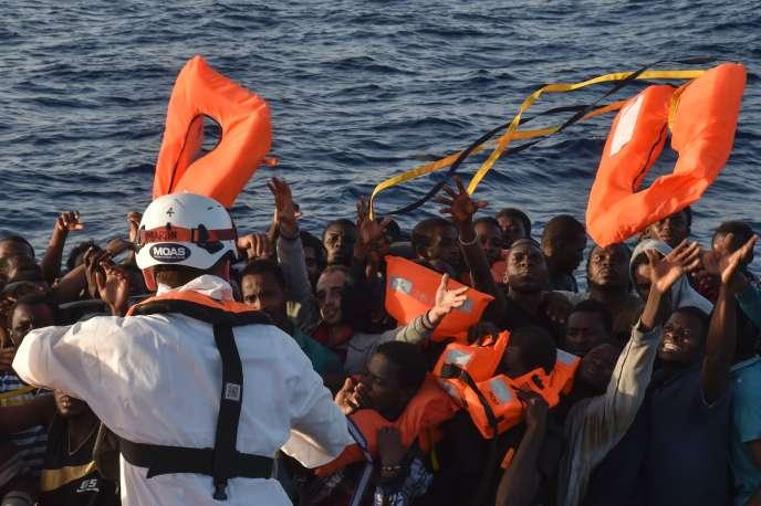 Des secouristes de l'ONG maltaise MOAS lancent des gilets de sauvetage à bord d'une embarcation de fortune au large de Libye, le 3 novembre 2016.