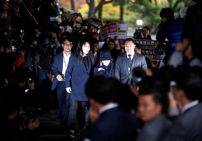 Choi Soon-sil, dissimulée sous un chapeau noir, à son arrivée au bureau des procureurs de Séoul, lundi 31 octobre.
