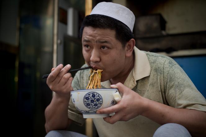Un chinois musulman rompt le jeune de ramadan assis devant une mosquée, à Pékin, le 1er juillet.