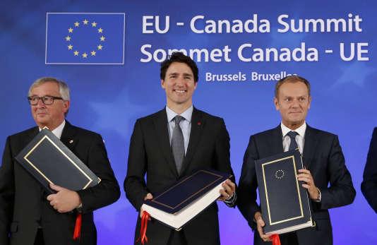 Les présidents européens Jean-Claude Juncker (à gauche) et Donald Tusk (à droite) aux côtés du premier ministre canadien Justin Trudeau lors du sommet de signature du CETA à Bruxelles, le 30 octobre.