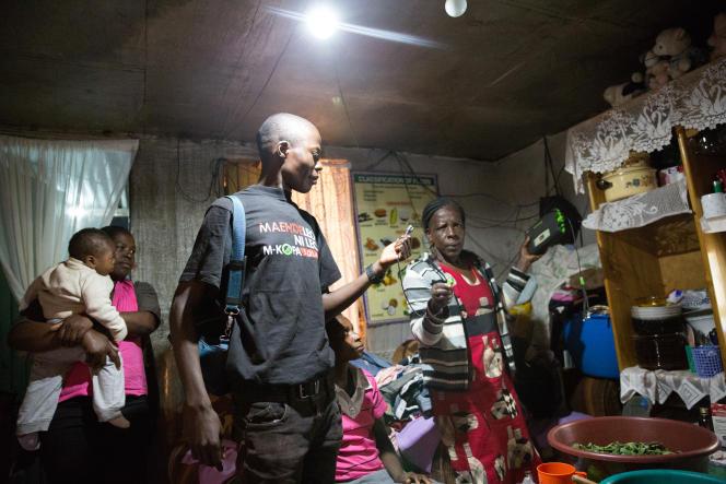 Un technicien de M-Kopa vérifie l'état du kit solaire de Scholastica.