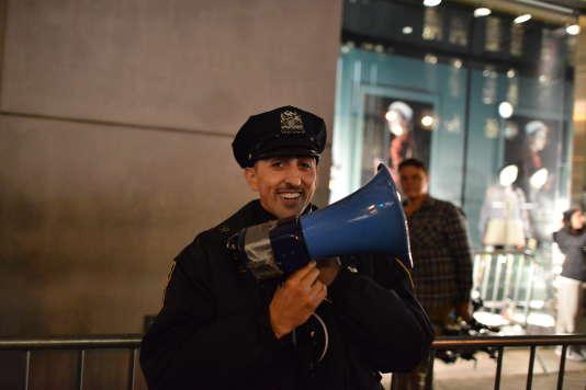 A l'aide d'un mégaphone, un agent de la police de New York demande aux passants de ne pas s'arrêter.