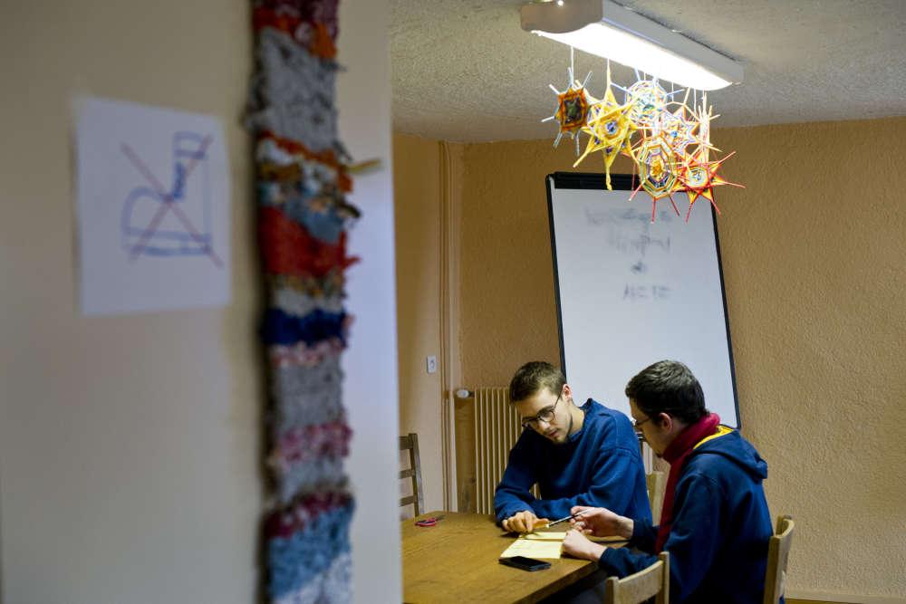 Simon et Daniel, bénévoles au sein de la communauté, préparent le cours de francais qu'ils dispenseront auprès des jeunes migrants.