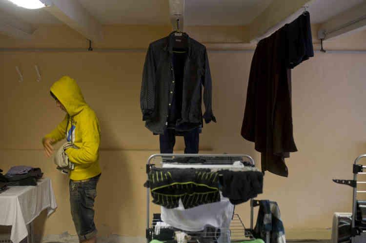 Mohammed plie méticuleusement son linge en discutant avec un camarade soudanais. A leur arrivée, les mineurs ont pu laver le peu de vêtements qu'ils avaient avec eux. Pour certains, ils n'avaient même pas de rechange.