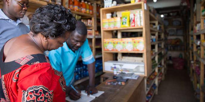 Penina et Jacob négocient avec Isaac, un commerçant de Nairobi, pour qu'il accepte de vendre les kits D. Light dans son magasin.