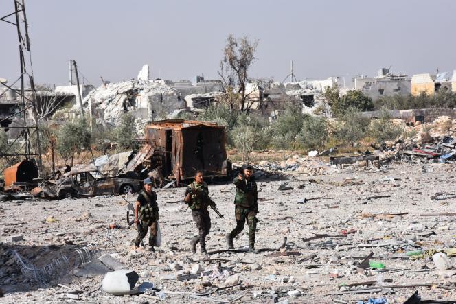 Des soldats du régime marchent dans un village récemment repris aux rebelles, à l'ouest d'Alep.