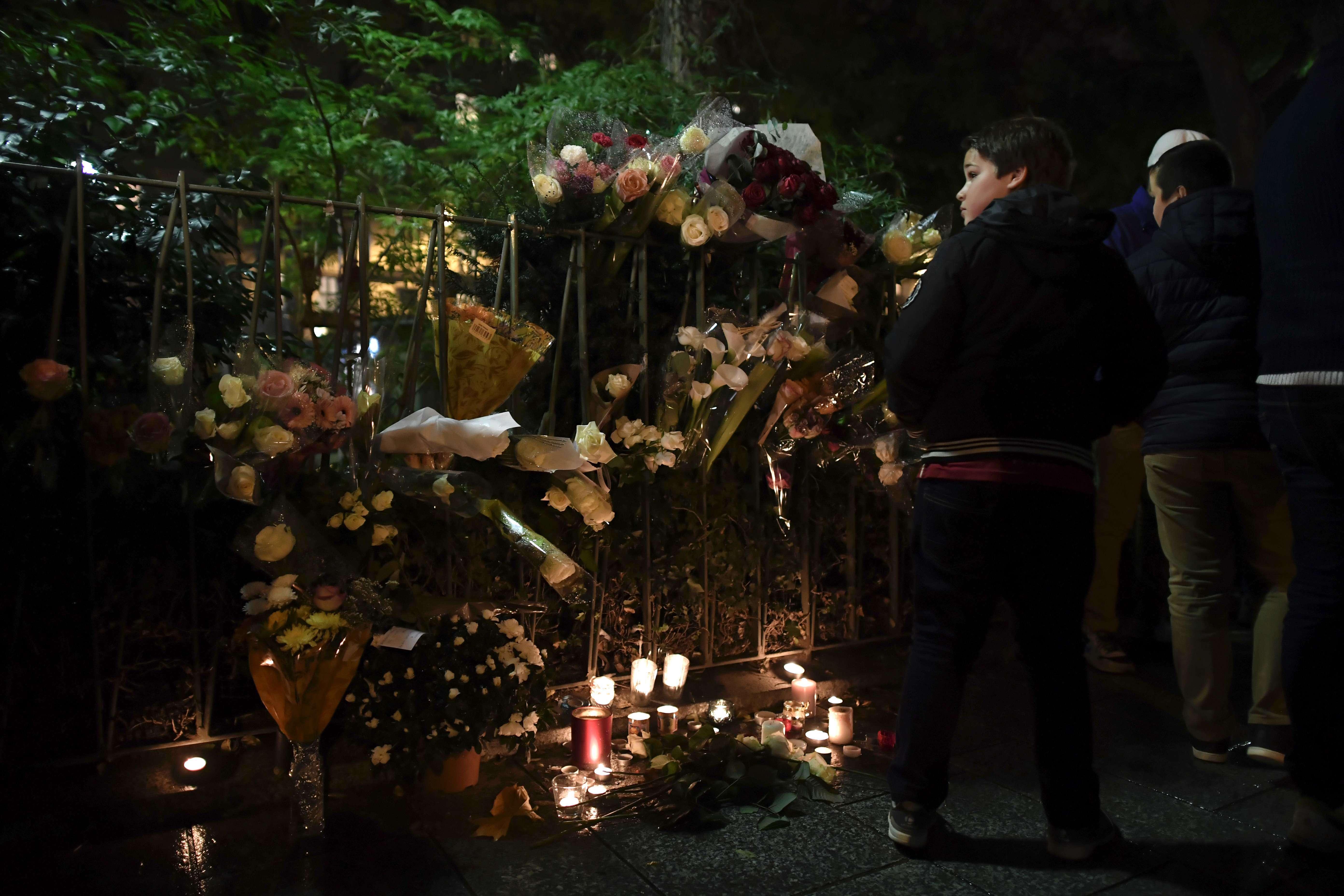 A proximité de l'entrée, bouquets de fleurs, bougies et messages rendent hommage aux victimes des trois djihadistes qui avaient fait irruption dans le Bataclan un an auparavant.