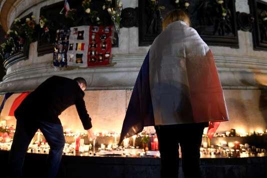 Un an après les attentats du 13 novembre2015 à Paris, des passants se recueillent place de la République, à Paris.