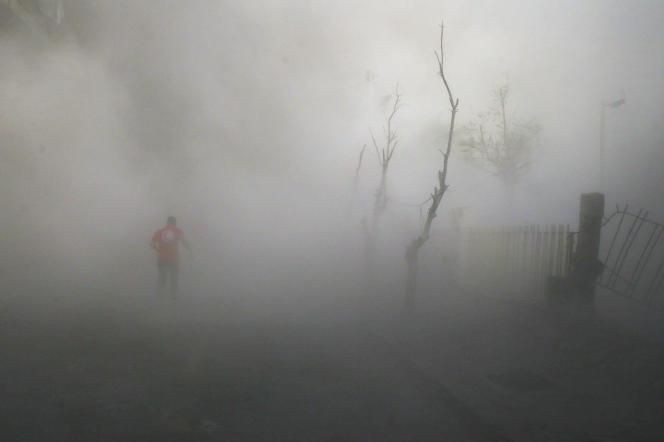 Un membre du Croissant rouge traverse un nuage de poussière après un bombardement sur la ville de Douma, dans la banlieue de Damas, le 8 novembre 2016.