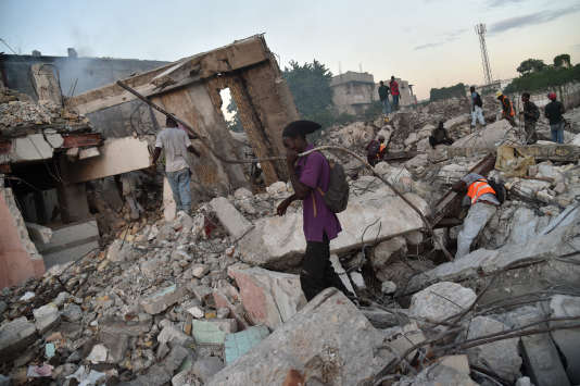 Des Haïtiens récupèrent du métal, des branchages et des briques dans les décombres d'un bâtiment de Port-au-Prince, le 2 novembre 2016.